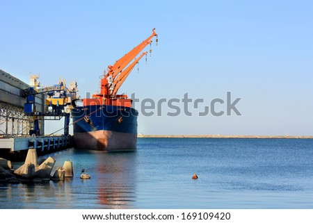 Port berth with material handling equipment and cargo ship at anchor - stock photo