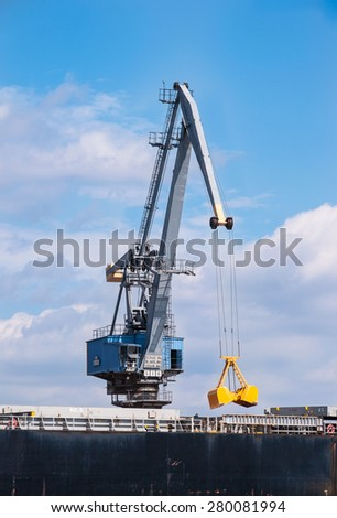 Port crane in Gdansk, Poland, with the open grabbing bucket loading / unloading the ship - stock photo