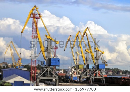 port cranes against the blue sky with clouds