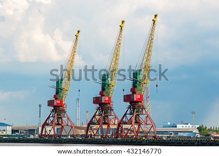Port cranes are waiting for a cargo ship