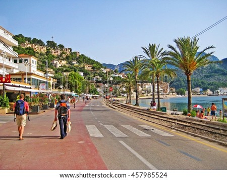 Port de Soller, Majorca, Spain - June 23, 2008: View of main street in Port de Soller - railroad tracks and promenade with palm trees and hotels aside. Two walking people in front.