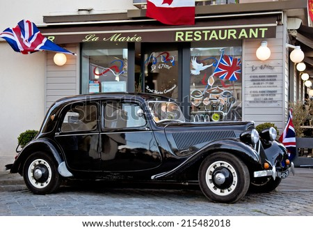 PORT-EN-BESSIN, FRANCE - JUNE 7: A French Resistance Citroen automobile as used by the maquis is parked outside of a WW2 festooned cafe for public display on June 7, 2014 in Port-en-Bessin.  - stock photo