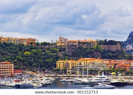 Port Hercule harbor, luxury ships and yachts and Palace of Prince of Monaco on the mountain in the Monaco (Monte Carlo) in summer