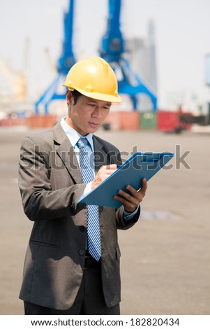 Port inspector recording the embarkation of seaport in notepad - stock photo
