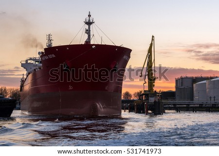 Port of Amsterdam, Noord-Holland/Netherlands -December 03-12-2016- Tugboat is assisting tanker Hafnia Soya at departure. The vessel is leaving port during a nice sunset. Nice maritime background
