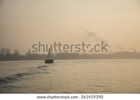Port of Amsterdam, Noord-Holland/Netherlands - March 17-03-2015 - Buoy with small wave in front. photo taken by sunrise with orange sky and foggy background. - stock photo