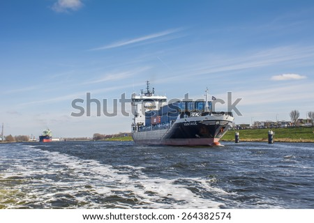 Port of Amsterdam, Noord-Holland/Netherlands - March 22-03-15 - Container vessel Vantage is loaded in Amsterdam and is sailing to the lock of IJmuiden. Cloudy sky at the background. - stock photo