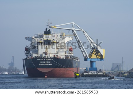 Port of Amsterdam, Noord-Holland/Netherlands - March 09-03-15 - Motor vessel Darya Shree is moored at the bollards. Floating crane Cornelis Tromp is in between and is loading the vessel with granite.  - stock photo