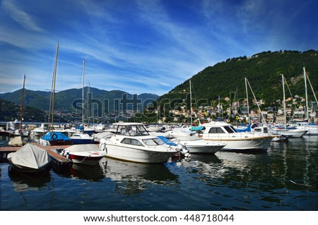 Port of Como lake with sailing boat and yacht