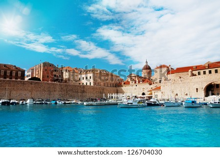 Port of Dubrovnik from water in sunny day with boats parked to the peer - stock photo