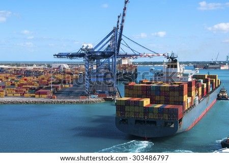 Port of Freeport Bahamas Container shipyard with heavy lifting Cranes and a ship coming in to dock assisted by tug boats