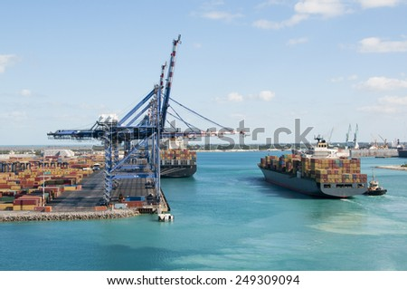 Port of Freeport Bahamas Container shipyard with heavy lifting Cranes and a ship waiting to off load its cargo - stock photo