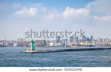 Port of Naples, coastal cityscape with green lighthouse tower on the pier - stock photo
