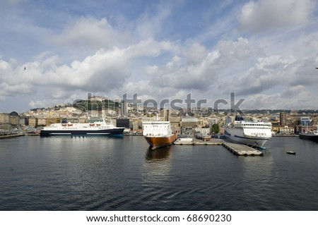 Port of Naples, Italy in Europe with ships and boats in the harbor and buildings and houses in the background.