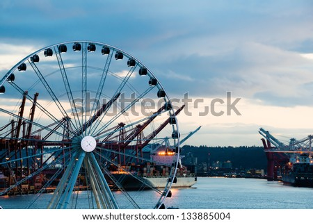 Port of Seattle with sea going cargo ships and Great Ferris Wheel at twilight. Copy space. - stock photo