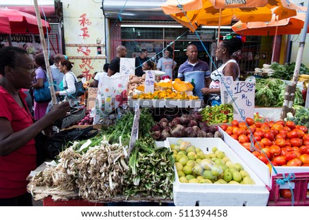 Port of spain, Trinidad and Tobago - November 28, 2015: fresh vegetables and fruit displayed for sale on local south market outdoors on streetscape background
