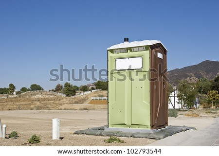 Porta Potty in a unfinished development construction site. - stock photo