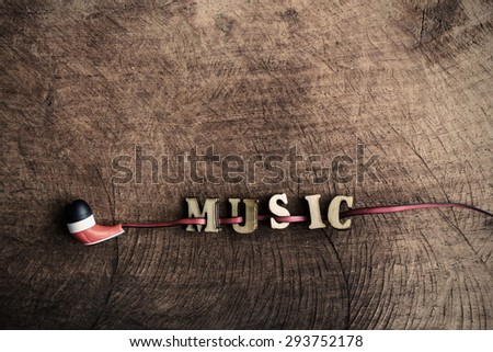 "portable audio earphones on old wood textured with word ""music"" - stock photo"