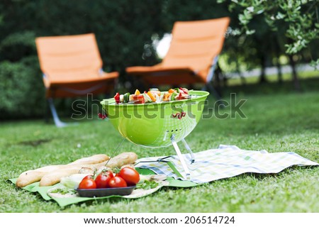 portable barbecue standing on a green lawn  during a picnic or summer camping trip  - stock photo