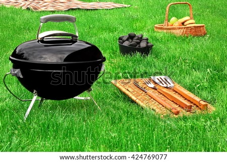 Portable BBQ Grill,  Charcoal Briquettes,Barbecue Tools, Basket With Snack And Fruits, Blanket  On The Fresh Green Lawn, Summertime Picnic Or Cookout Concept