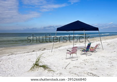 Portable Blue Canvass Shelter with Chairs  Set up on the Beach   - stock photo