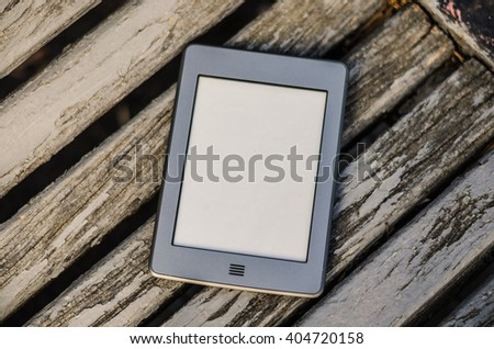 Portable electronic book lying on a bench in the park - stock photo