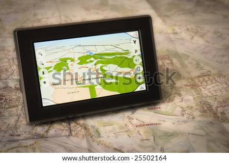 Portable GPS for a car sitting on a map - stock photo