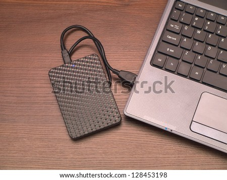 portable hard drive and laptop computer - stock photo
