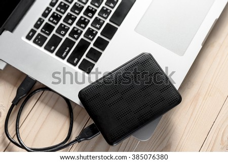 portable hard drive and laptop computer, External hard disk and laptop computer - stock photo