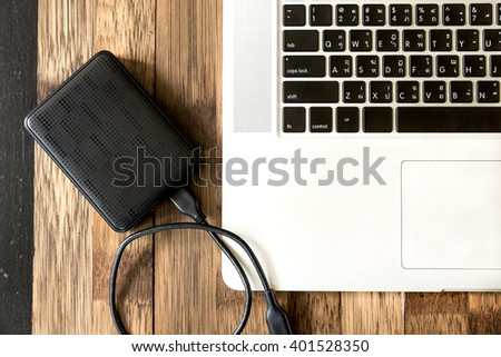 portable hard drive and laptop computer, External hard disk and laptop computer, with selective focus - stock photo