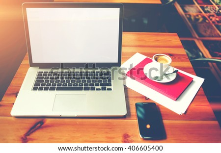 Portable net-book and smart phone with blank copy space screen for your text message or promotional content, laptop computer with cell telephone lying on a table in cafe, distance work via internet  - stock photo