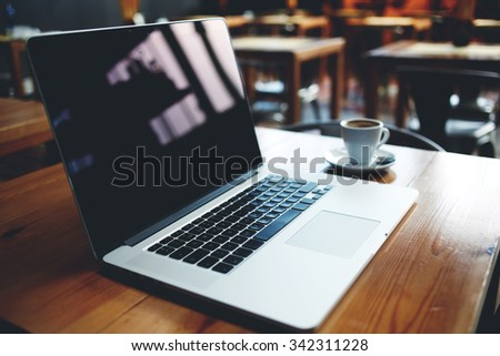 Portable net-book with copy space screen for your text message or promotional content, open laptop computer and cup of coffee lying on wooden table in modern cafe bar interior during morning breakfast - stock photo