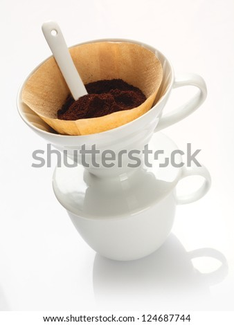 Portable plain white china filter funnel with filter paper filled with freshly ground coffee beans and a measuring spoon - stock photo