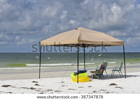 Portable Shelter with Chairs and Floatation Devices on the Beach  - stock photo