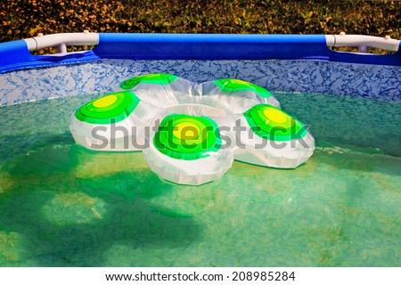 Portable the convenient swimming-pool for the children, located in the house yard, on a water surface floats a rubber ring. - stock photo