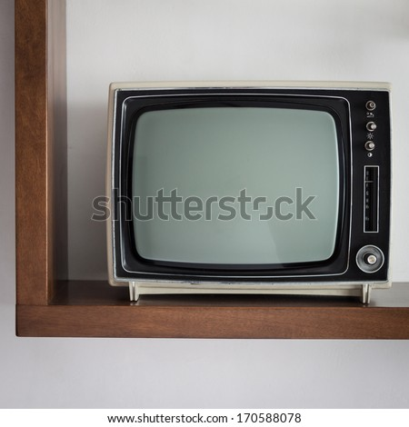 Portable vintage television on a shelf - stock photo
