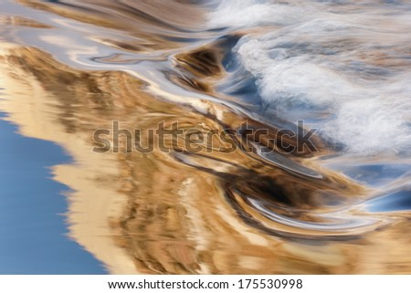 Portage Creek cascade captured with motion blur and illuminated by reflected color from sunlit trees and blue sky overhead, Michigan, USA  - stock photo