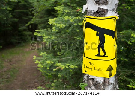 Portage sign on birch tree marking route in Algonquin Park - stock photo