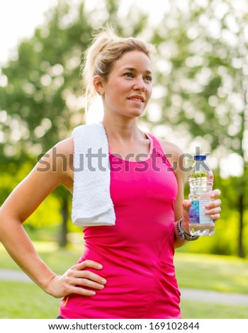 Portait of a beautiful active girl keeping hydrated by drinking water during her workout under trees - stock photo