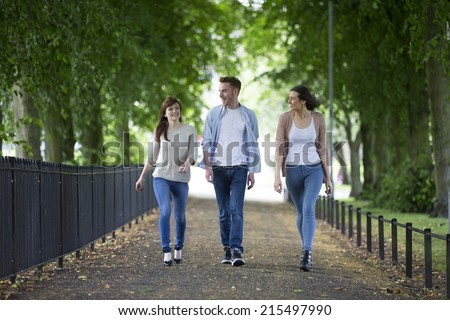 Portait of a group of students walking together outside in urban area. Three caucasian men and women walking at a university campus. - stock photo
