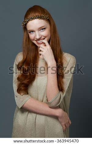 Portait of a smiling cute redhead woman standing over gray background and looking at camera - stock photo