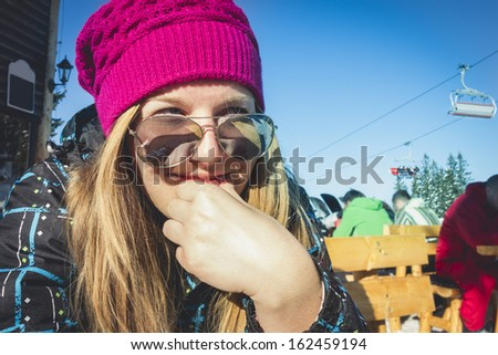 Portait of a young beautiful girl wondering which ski track she should take to ride this time while having a coffee brake.  - stock photo