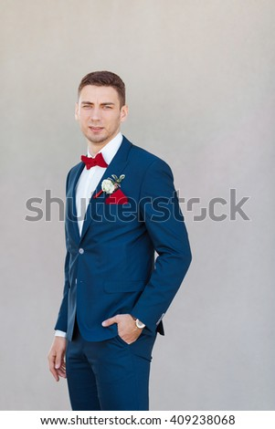 Portait of a young handsome man in suite. Close up of a gorgeous guy on gray background - stock photo