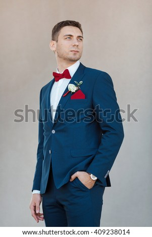 Portait of a young handsome man in suite. Gorgeous guy on gray background - stock photo