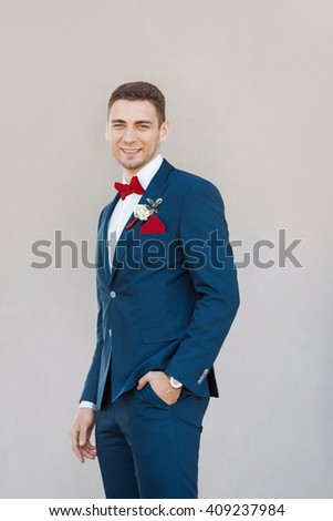 Portait of a young happy handsome man in suite. Gorgeous guy on gray background - stock photo