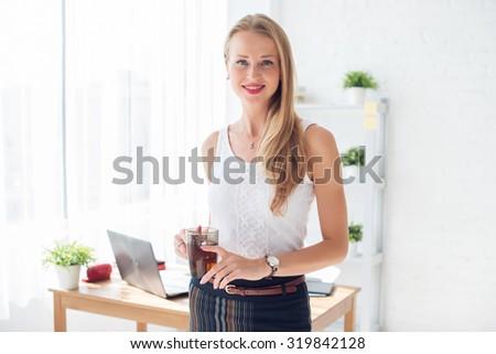 Portait of beautiful successful business woman holding cup of coffee looking at camera.