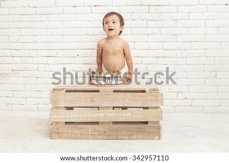 portait of cheerful adorable toddler with his cake on white walls background - stock photo