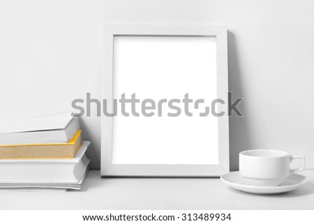 portait of white desk with blank photo frame, books, and coffee cup with white background - stock photo