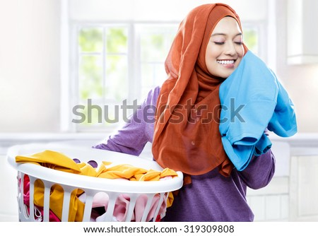 portait of young woman wearing hijab carrying laundry basket while smelling fresh clean clothes - stock photo