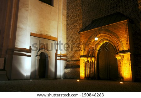 portal to gothic church by night in Poznan, Poland